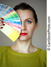 Woman with a red lips looking to a color paint palette -...