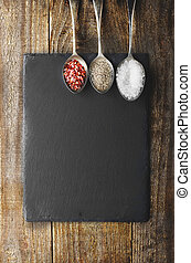 Dray spices on metal spoon on black stone with copy space....