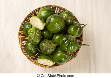 Some green african eggplants over a white background....