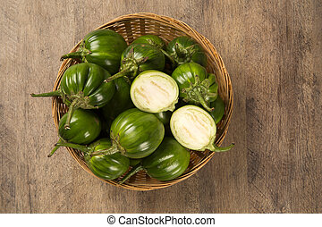 Some green african eggplants over a wooden surface....
