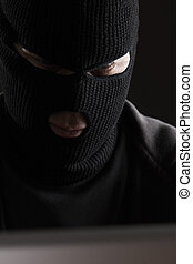 Masked Criminal Accessing Computer Data