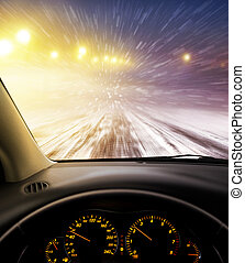 snow-covered road at night - view through car windshield to...