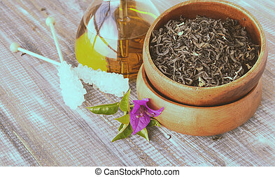 Green tea in a wooden bowl with flowers