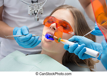 Tooth filling ultraviolet lamp - Girl patient in the dental...