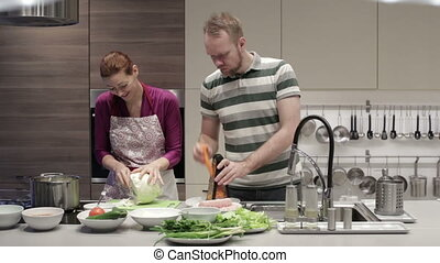 Man and woman cut vegetables in the kitchen