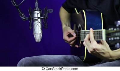 Playing Acoustic Guitar in Studio - Man playing guitar in...