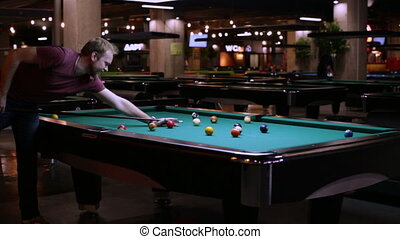 Human playing in pocket billiards - Young man playing pool...