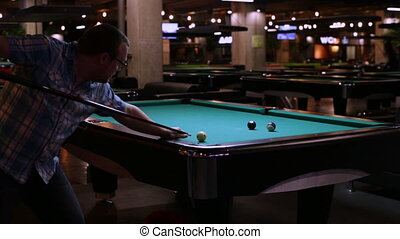 Adult man playing in pocket billiards - Young man playing...
