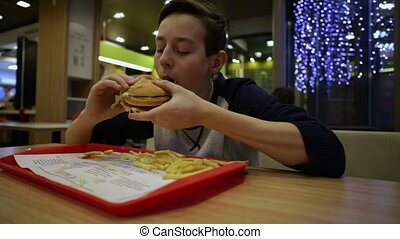 Teen boy in the cafeteria eating Hamburger