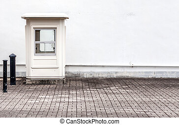 Empty guard post next to a white wall
