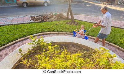Grandpa Pushes Tricycle with Little Girl Reads Smartphone in...