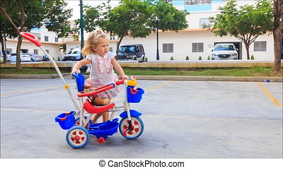 Little Blond Girl Pushes Pram Tricycle about Play Ground -...