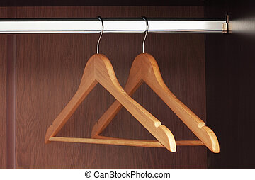 Hangers - Wooden hangers hanging in an empty closet on the...