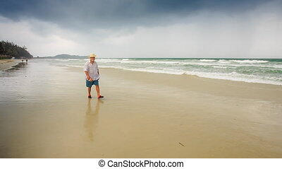 Bearded Old Man in Hat Goes along Wet Sand by Wave Surf