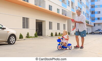 Grandpa Pushes Tricycle with Little Girl Reads Smartphone -...