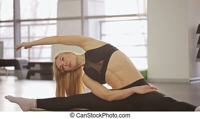 A woman athlete doing stretching workout overall in the gym...