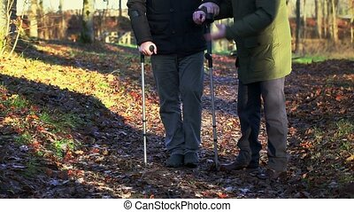 Disabled man on crutches with assistant