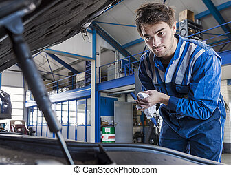 Car mechanic under the hood - Mechanic looks under the hood...