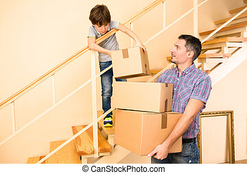 Family moving into a new house - Little boy helping his...