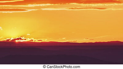 sunset scene with sun fall behind the mountains and clouds in background time lapse, warm colorful sky with soft clouds 4K and HD