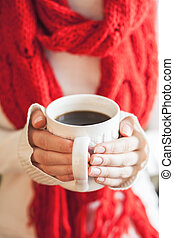 Woman hands holding a mug with hot coffee.