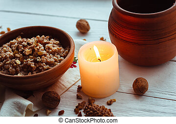Christmas porridge with candles on white wooden background