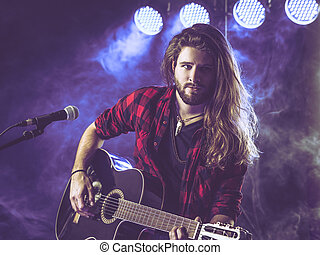 Playing acoustic guitar on stage
