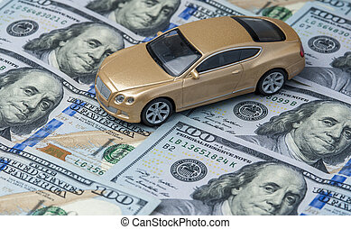 Golden toy car on the background of banknotes - Golden toy...