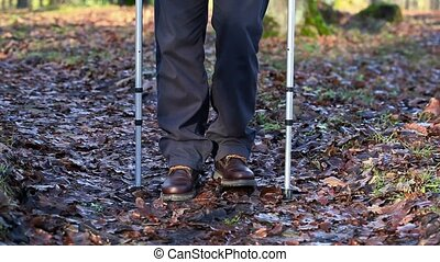 Disabled man on crutches at outdoor on the path in the park...
