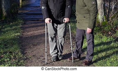 Disabled man on crutches with assistant at outdoor