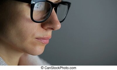 Woman in glasses surfing internet on computer close-up