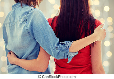 close up of happy lesbian couple hugging at home - people,...