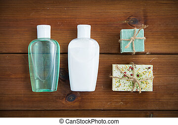 close up of handmade soap bars and lotions on wood - beauty,...
