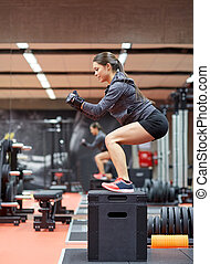 woman doing squats on pnatfom in gym - fitness, sport,...