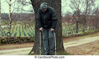Disabled man with crutches  in graveyard.