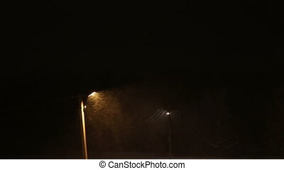 Snow storm at night on the background of a lamppost. -...