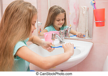 Girl rinse the toothbrush under running tap water - Six year...