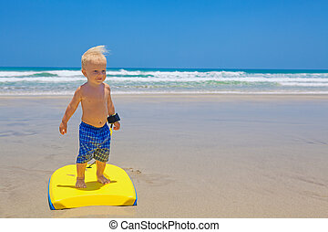 Little child swimming with bodyboard on the sea sand beach -...