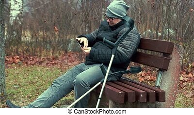 Disabled man with crutches and tablet PC on bench