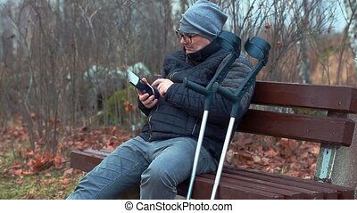 Disabled man with crutches and smartphone on bench