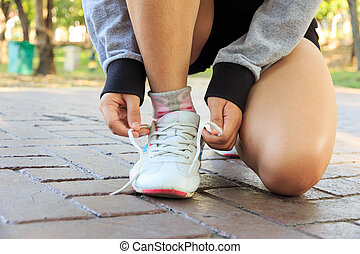 Female athlete tying laces for jogging on road
