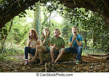 Group Of Children Eating Sausages In Woodland Camp