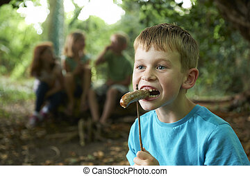 Boy Eating Sausage Cooked On Campfire With Friends