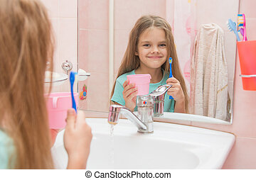 Happy little girl standing with toothbrush and cup and looks...