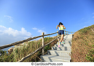 young fitness woman trail runner running up on mountain...