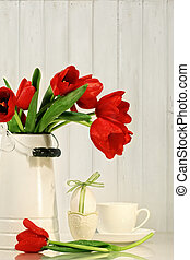 Tulips and egg with bow on table