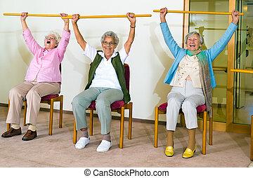 Three happy elderly ladies doing exercises in a seniors gym...