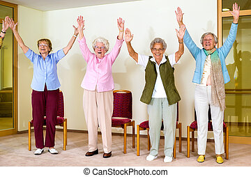 Happy enthusiastic group of senior women doing a physical...