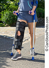 Woman wearing a leg brace walking on crutches - Woman...