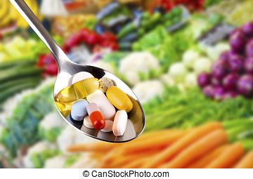 spoon with pills, dietary supplements on vegetables...